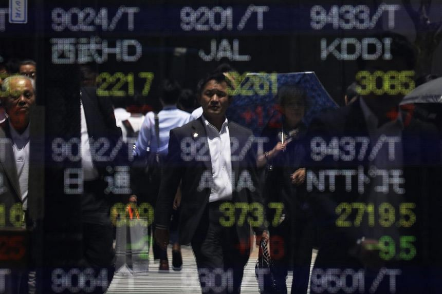 Pedestrians are reflected on an electronic stock board at a securities firm in Tokyo, Japan.