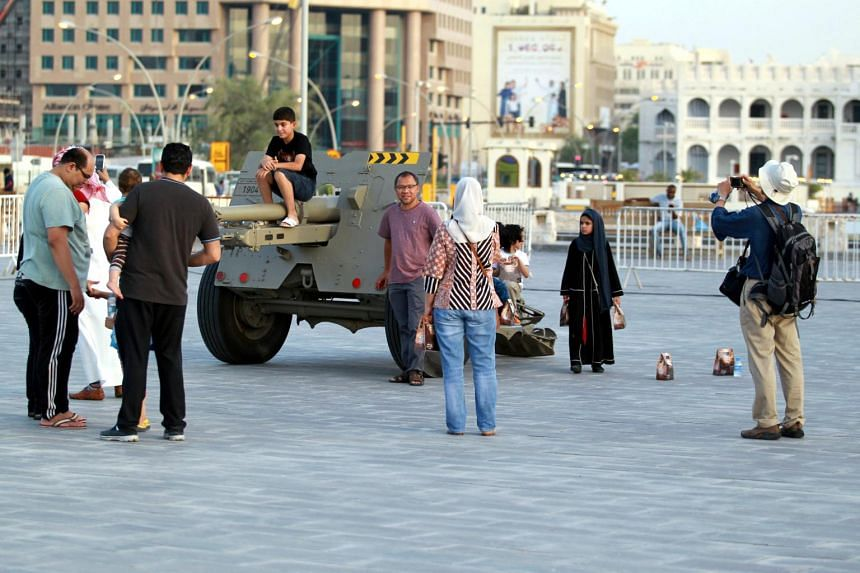 People take pictures next to a traditional Ramadan cannon in Doha.
