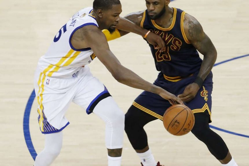 Golden State Warriors forward Kevin Durant (left) tries to drive by Cleveland Cavaliers forward LeBron James.