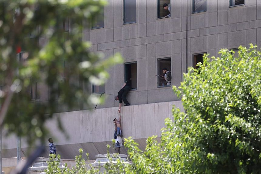 Civilians fleeing from Iran's Parliament building with help from policemen on Wednesday (June 7).