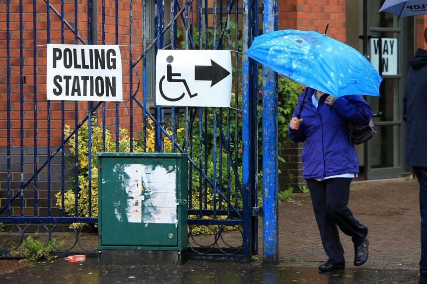 Voters leaving after casting their ballot at a polling station in west Belfast, Northern Ireland, on June 8, 2017.
