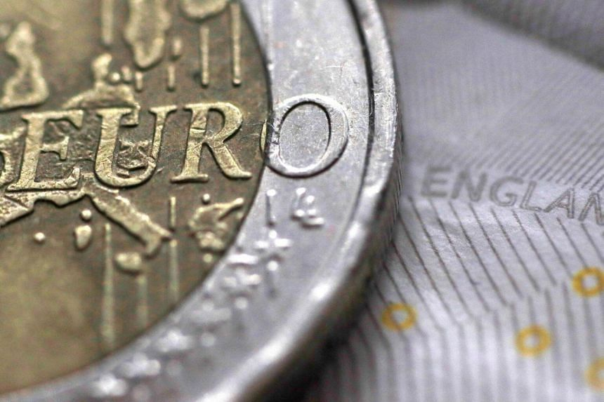 A two Euro coin is pictured next to an English ten Pound note in an illustration.