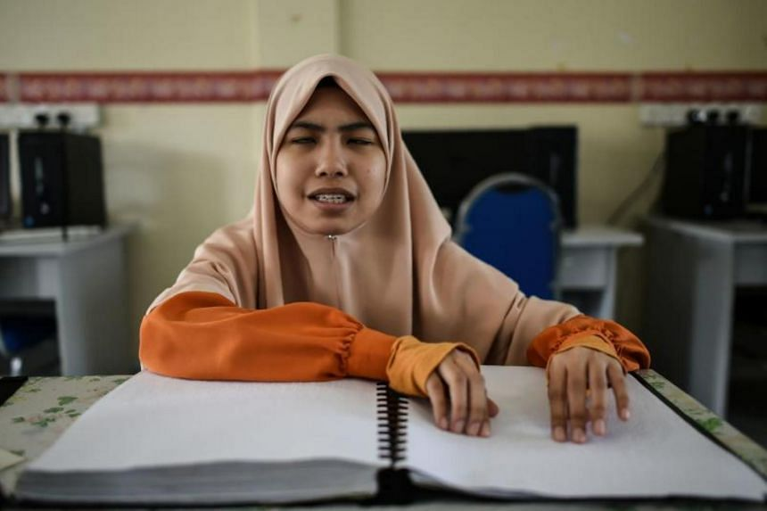 A visually impaired Malaysian Islamic studies student reading and memorising the Quran from a Braille copy of the holy book at the Darul Quran academic institution in Kuala Kubu Bharu.