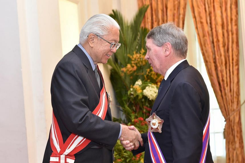President Tony Tan Keng Yam congratulating Former Australian Secretary of Defence Dennis James Richardson after conferring on him Singapore's highest military award, the Darjah Utama Bakti Cemerlang (Tentera) [Distinguished Service Order (Military)],