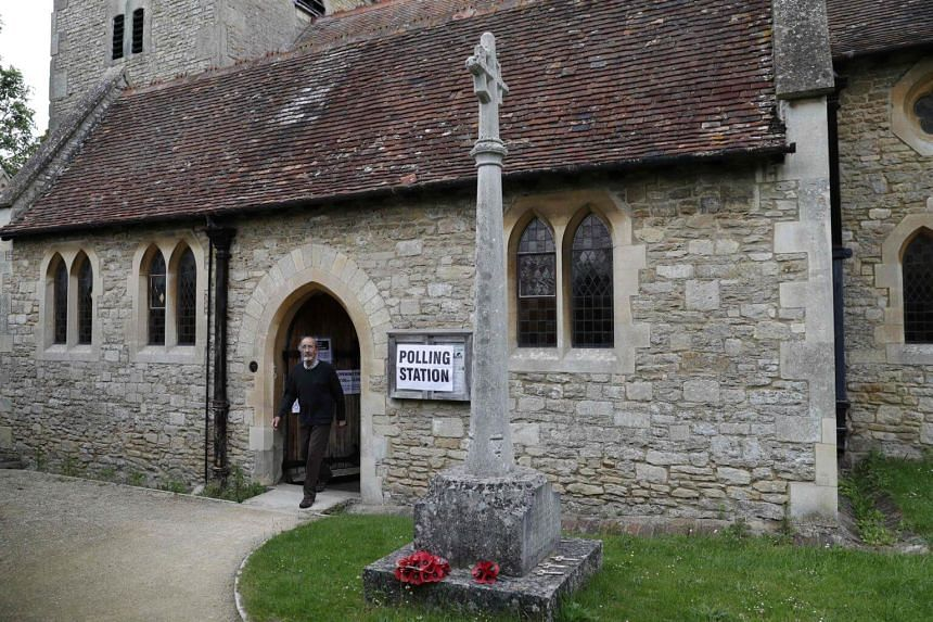 A voter leaving a church set up as a polling station in Stadhampton, near Oxford, west of London, on June 8, 2017.