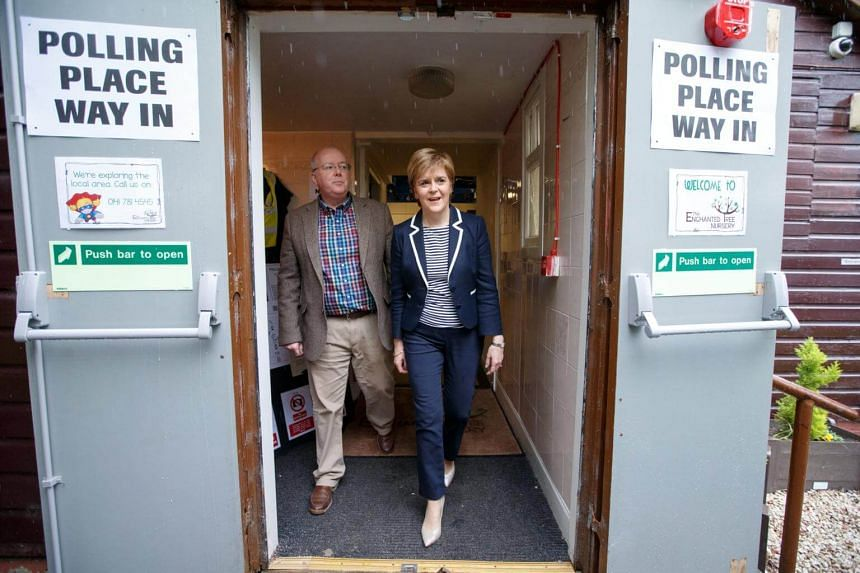 Scottish National Party leader Nicola Sturgeon (right) with her husband Peter Murrell after casting their votes at a polling station at Broomhouse Community Hall, in Glasgow, Scotland, on June 8, 2017.