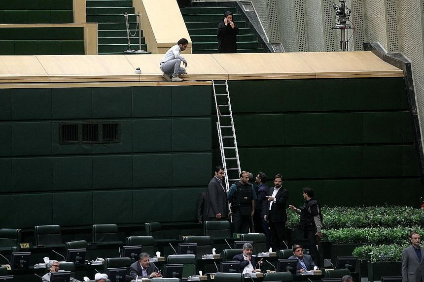 This photo, provided by a third party, shows members of the Iranian government forces swinging into action during the attack at the Parliament building in central Teheran yesterday morning. Policemen being deployed inside Parliament to protect lawmak