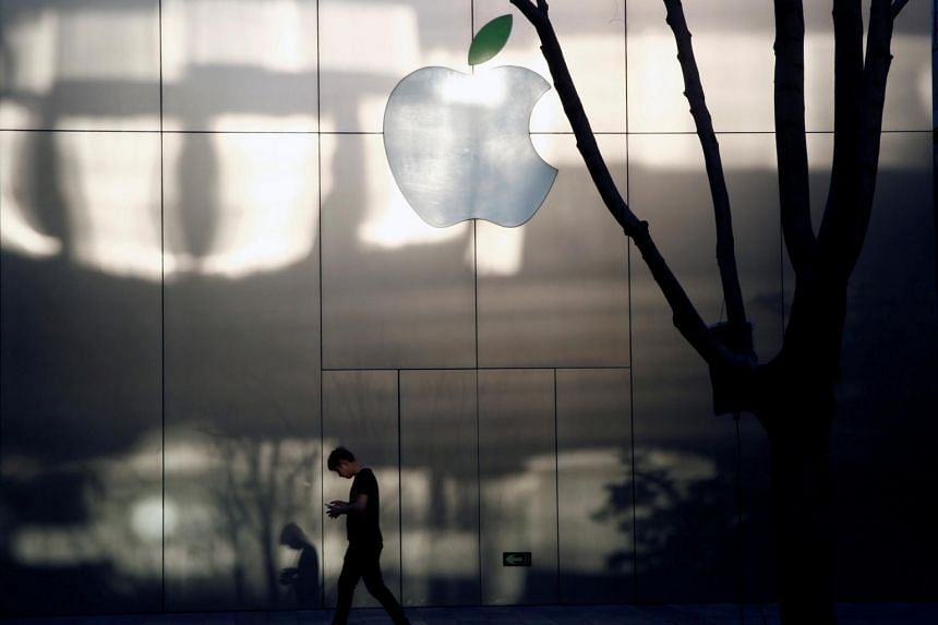 A man uses his phone as he walks past an Apple store in Beijing, China on April 25, 2017.