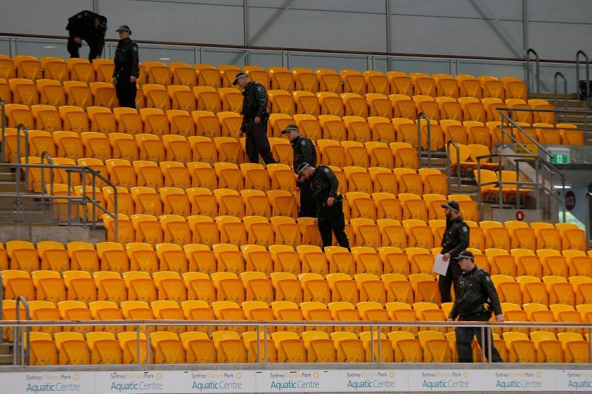 Australian police inspect seat rows for explosives at the Sydney Olympic Park Aquatic Center in Sydney, Australia, on June 8, 2017.