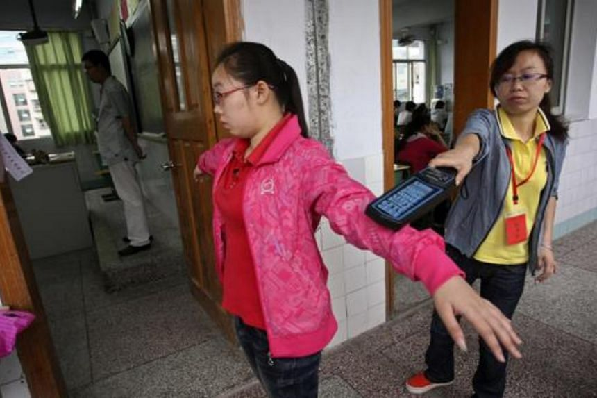 A student being subjected to checks during the national college entrance examination at a high school in Sichuan province.