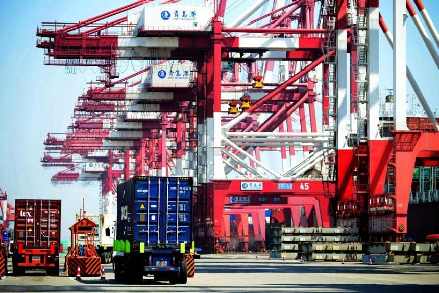 Trucks transport shipping containers at a port in Qingdao, east China's Shandong province.