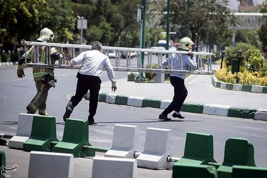 Members of Iranian civil defence run during an attack on the Iranian parliament in central Teheran, Iran, on June 7, 2017.
