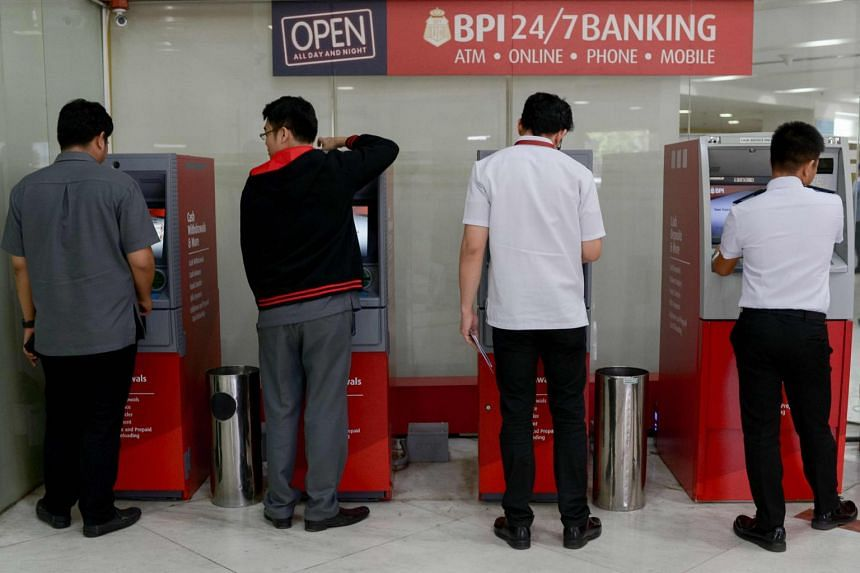 People trying to check their balances on automated teller machines at a branch of the Bank of the Philippine Islands in Manila on June 8, 2017.