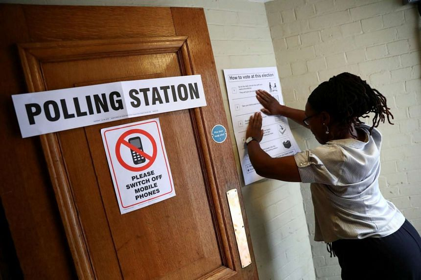 A worker prepares signs outside a polling station on general election day in London, Britain on June 8, 2017.
