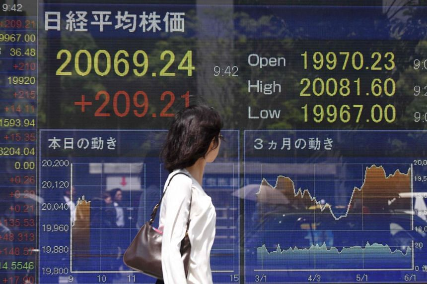 A woman looks at a stock quotation board flashing the key Nikkei index of the Tokyo Stock Exchange in front of a securities company in Tokyo.