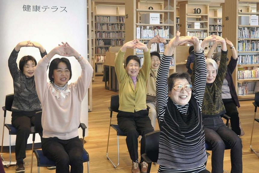 Women exercising next to bookshelves filled with health-related books at the Yamato City Library in Kanagawa Prefecture.