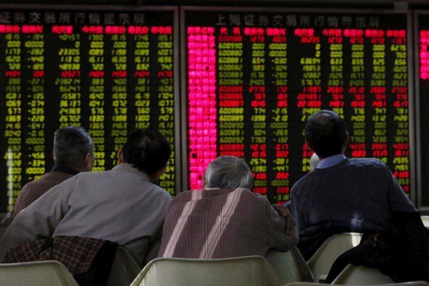 Men look at an electronic board showing stock market information at a brokerage house in Beijing, China on Jan 5, 2016.