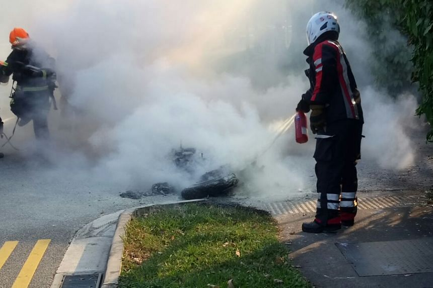 SCDF officers extinguish the motorcycle on fire.
