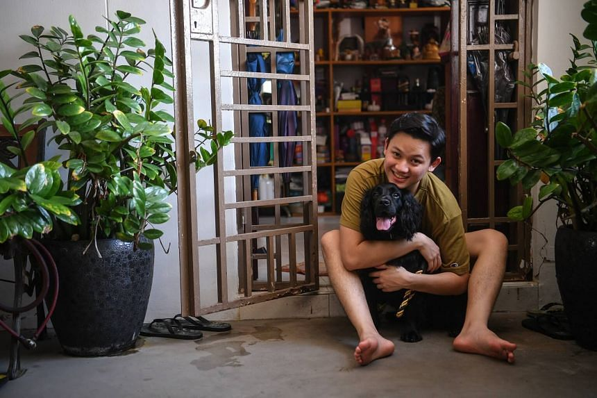 Thaksin Toh, 21, an ex-NSF who served in the police K-9 unit, pictured with his re-homed seven-year-old Cockel Spaniel (a retired K-9 service dog) at his house on June 9, 2017.