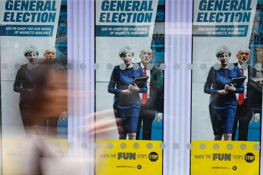 A woman walks past General Election themed posters with images of Britain's Prime Minister Theresa May and Labour party leader Jeremy Corbyn in London on June 8, 2017.