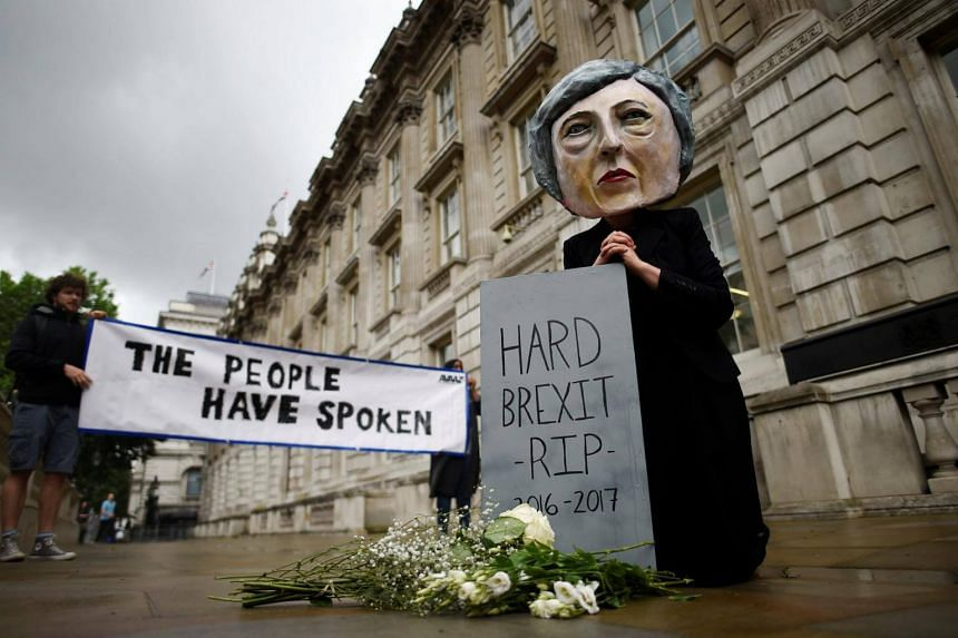 A protester wearing a Theresa May mask is seen the day after Britain's election in London, on June 9, 2017.