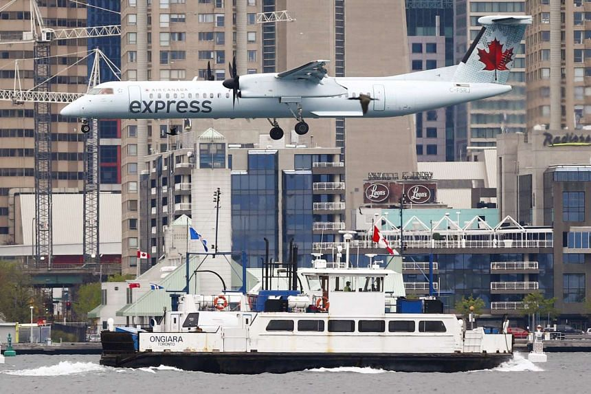 An Air Canada Express flight descends over a boat to land at the Billy Bishop Toronto City Airport, also known as the Toronto Island Airport, in Toronto, on May 12, 2015.