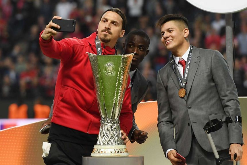 Injured players Zlatan Ibrahimovic (left), Eric Bailly (centre) and Marcos Rojo take a selfie with the Europa League trophy.