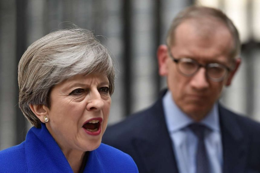 Theresa May addresses the country as her husband looks on after Britain's election.