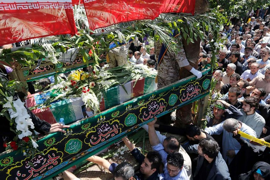 Iranians touch the coffins of victims who died in a terror attack, during their funeral in Tehran, Iran on June 8, 2017.
