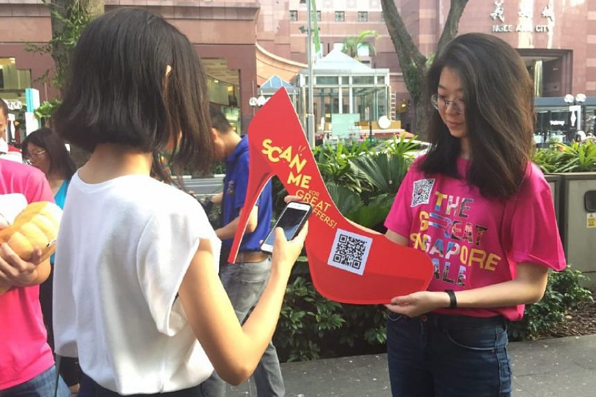 Student Alyssa Loo scanning a QR code embedded with GoSpree app deals outside Paragon at the GSS launch on June 9, 2017.