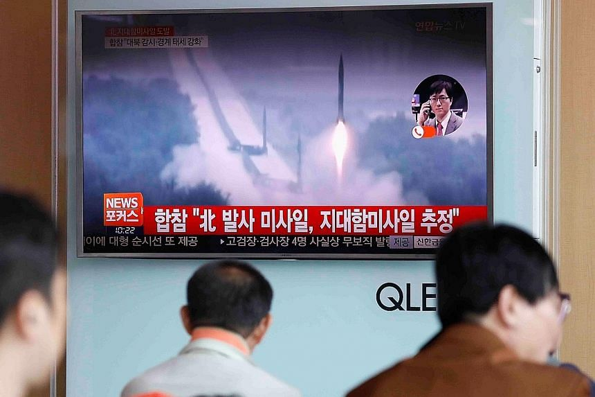 North Korea's launch of land-to-ship missiles being shown on TV at a Seoul railway station.