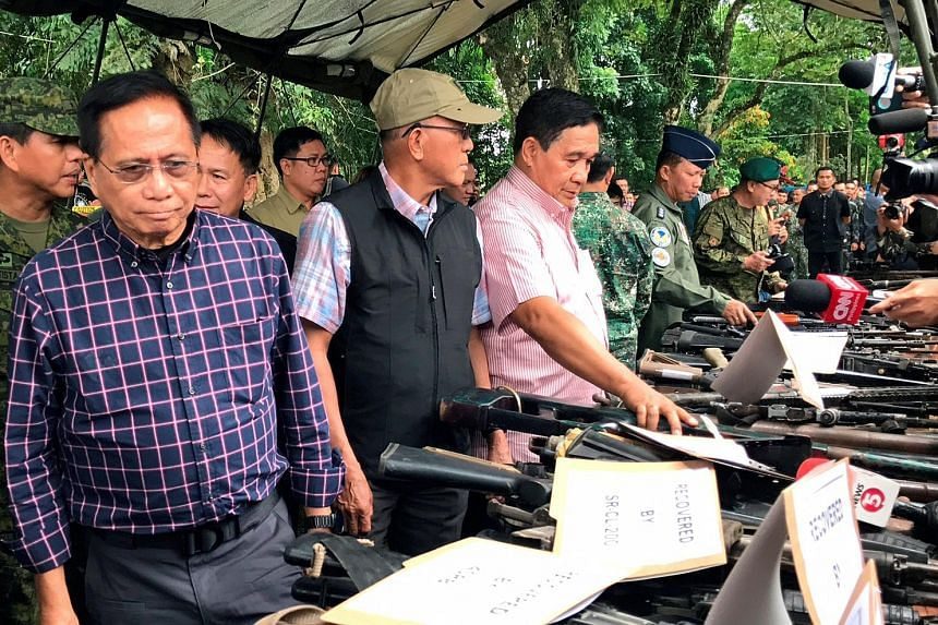 (From left) Presidential adviser on the peace process Jesus Dureza, Philippine Defence Secretary Delfin Lorenzana and National Security Adviser Hermogenes Esperon yesterday inspecting firearms seized in Marawi.