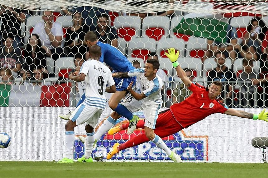 Uruguay goalkeeper Fernando Muslera diving in vain as defender Jose Gimenez (not in picture) scores an own goal in the friendly versus Italy. The Azzurri will be in a confident mood ahead of their World Cup qualifier against minnows Liechtenstein.