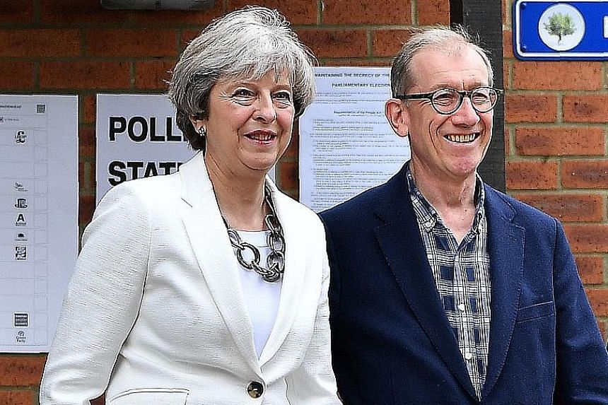 British Prime Minister Theresa May and her husband Philip, and main opposition Labour party leader Jeremy Corbyn, after casting their votes in London yesterday. More than 40,000 polling stations were open, with 46.9 million people registered to vote.