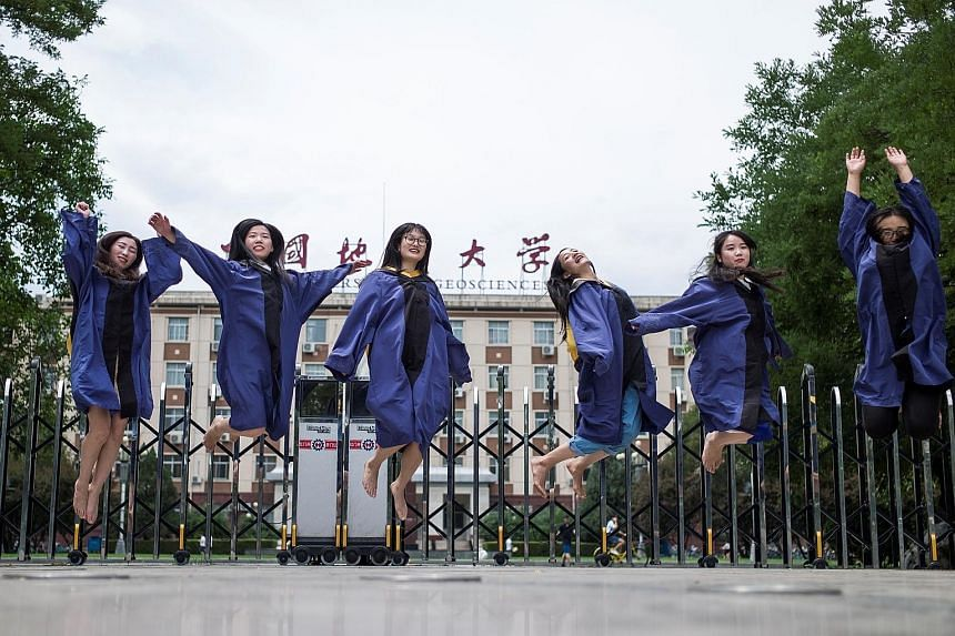 Graduates posing for a picture after earning their master's degrees from the China University of Geosciences in Beijing yesterday. The school is regarded as a top university and its notable alumni include Mr Wen Jiabao, the former premier, who attend