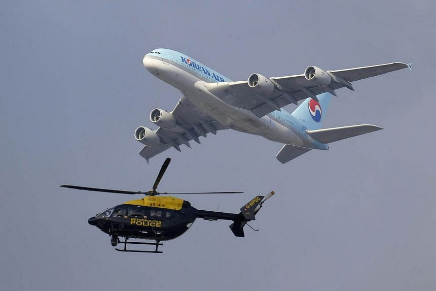 File photo of a Korean Air aeroplane as a police helicopter looks over the river Thames.