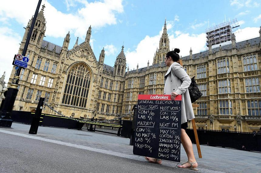 A betting shop worker carries a board displaying odds for scenarios in the general election outside the Houses of Parliament in Westminster, London.