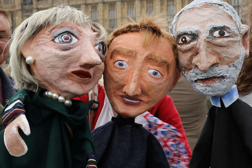 Performers pose with puppet caricatures of Prime Minister Theresa May, leader of the Liberal Democrat Party Tim Farron and leader of the Labour Party Jeremy Corbyn, in front of the Palace of Westminster in London on June 8, 2017.
