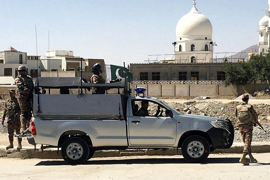Pakistani security officials inspect the area from where two Chinese nationals were abducted by unknown armed men, in Quetta, Pakistan.