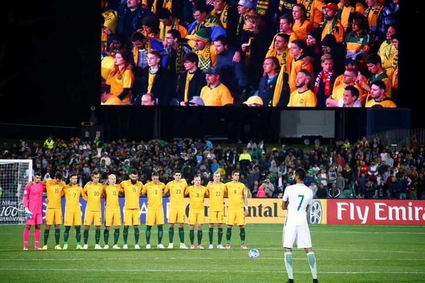 The Australian team stand together, as members of the crowd are shown on a large screen, as they observe a minute's silence for victims of the London attacks.