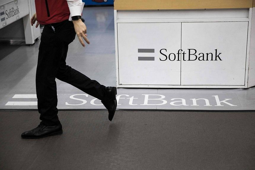 A man walks past a logo of Japanese mobile telecoms company SoftBank at a department store in Tokyo.