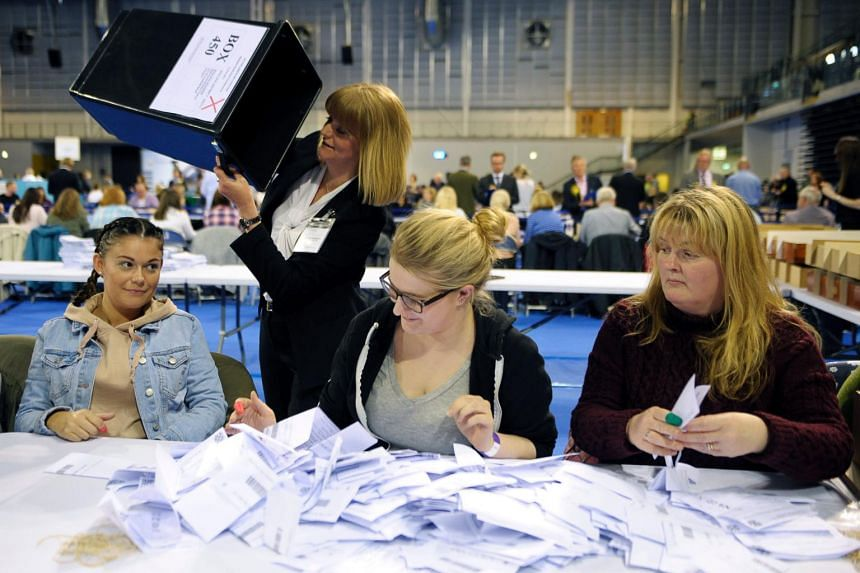 Counting staff members empty the first ballot boxes at the main Glasgow counting centre in Emirates Arena in Glasgow, Scotland, on June 8, 2017.