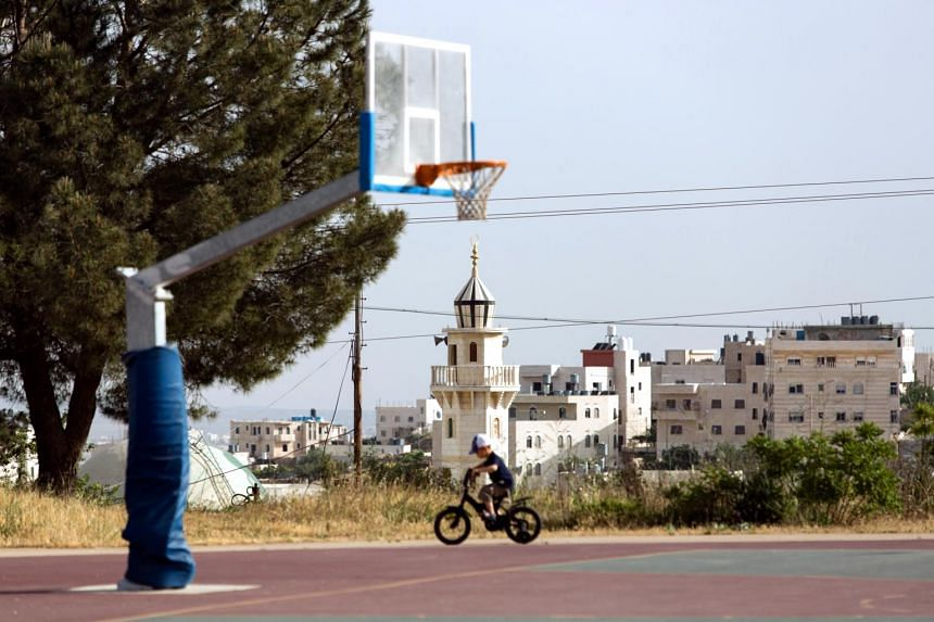 A mosque and homes in the Palestinian city of Hebron provide the backdrop as an Israeli child plays in the Kiryat Arba settlement, one of the oldest in the West Bank.