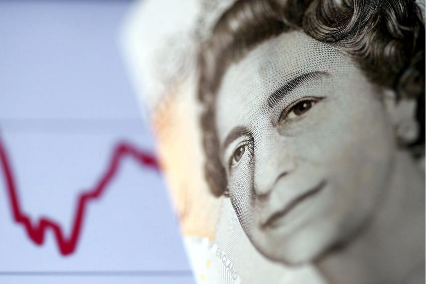A British ten pound note is seen in front of a stock graph in this illustration photo.