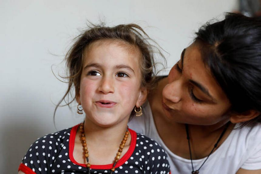 Iraqi Christina Ezzo Abada, a former hostage of Islamic State militants for three years, sits next to her sister inside a cramped home at a refugee camp in Erbil, Iraq, on June 10, 2017.