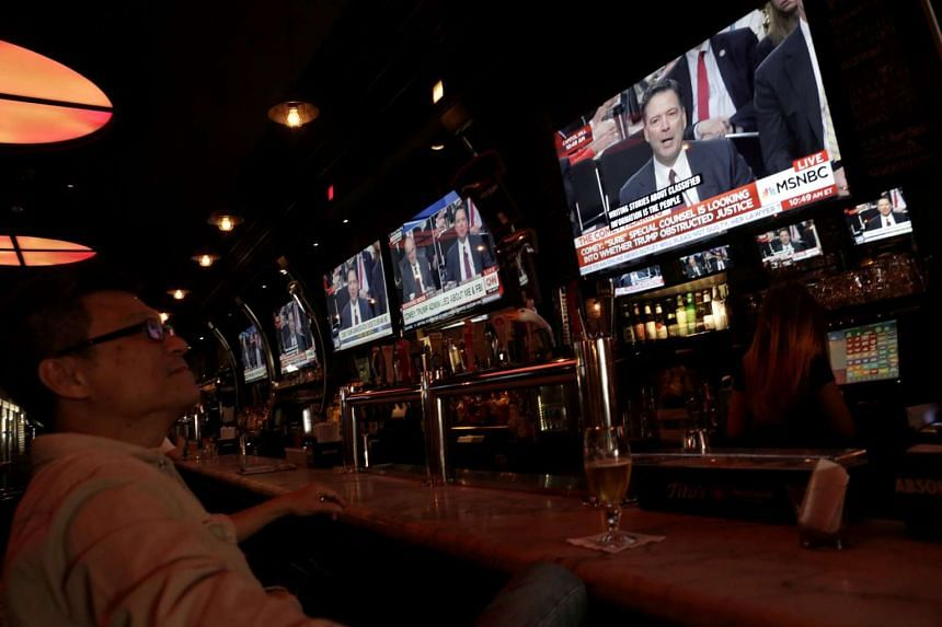 A man watches a television showing former FBI director James Comey's testimony before the Senate Intelligence Committee, in Tonic bar in New York City, US on June 8, 2017.