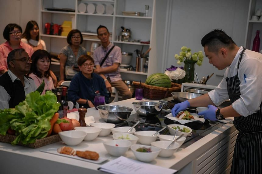 Participants at the farm-to-table event at One Farrer Hotel and Spa watch One Farrer Hotel and Spa executive chef Elson Cheong (right), 40, during a cooking demonstration on June 10, 2017.