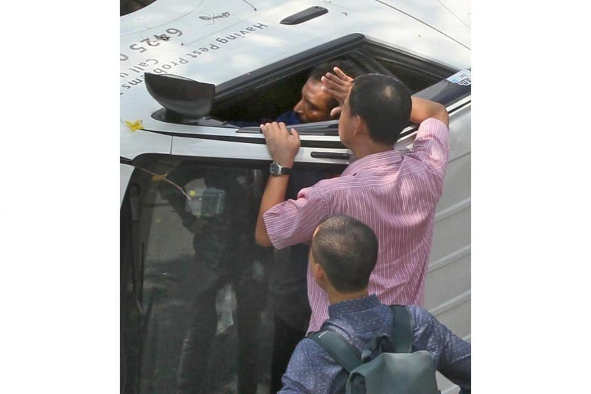 Along with other members of the public, Shin Min reporter Ren Qi (in blue) helped rescue a man trapped in a van.