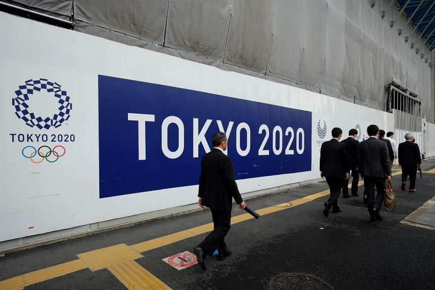 Pedestrians walk past the logo of Tokyo 2020 Olympic and Paralympic Games decorating a wall of a construction site in Tokyo on June 8, 2017.