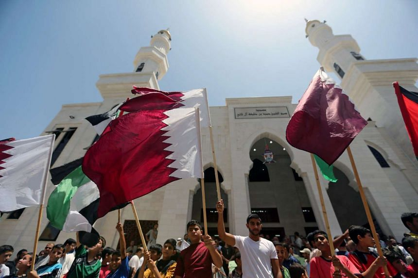 Palestinians rally for Qatar, at a Qatari-funded construction project in the southern Gaza Strip, June 9, 2017.